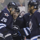 Winnipeg Jets' Blake Wheeler (26), Bryan Little (18) Dustin Byfuglien (33) and Andrew Ladd (16) celebrate Little's goal against the Phoenix Coyotes during second-period NHL hockey game action in Winnipeg, Manitoba, Thursday, Feb. 27, 2014. (AP Phoyo/The C