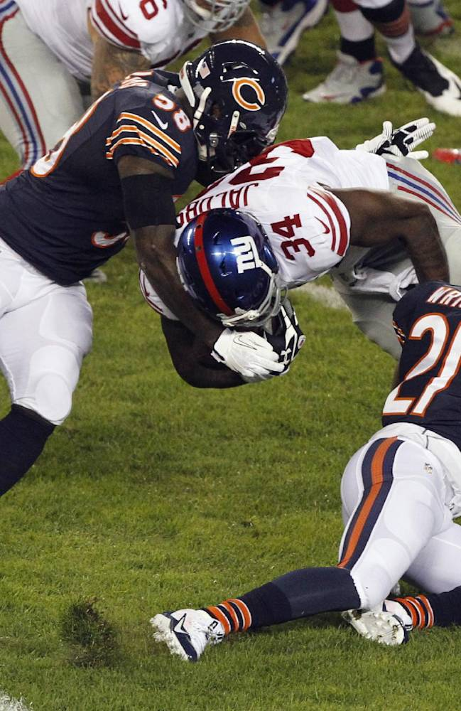 Chicago Bears linebacker D.J. Williams (58) and safety Major Wright (21) tackle New York Giants running back Brandon Jacobs (34) In the first half of an NFL football game, Thursday, Oct. 10, 2013, in Chicago
