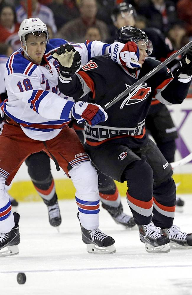 New York Rangers' Marc Staal (18) and Carolina Hurricanes' Alexander Semin (28) chase the puck during the second period of an NHL hockey game in Raleigh, N.C., Friday, March 7, 2014