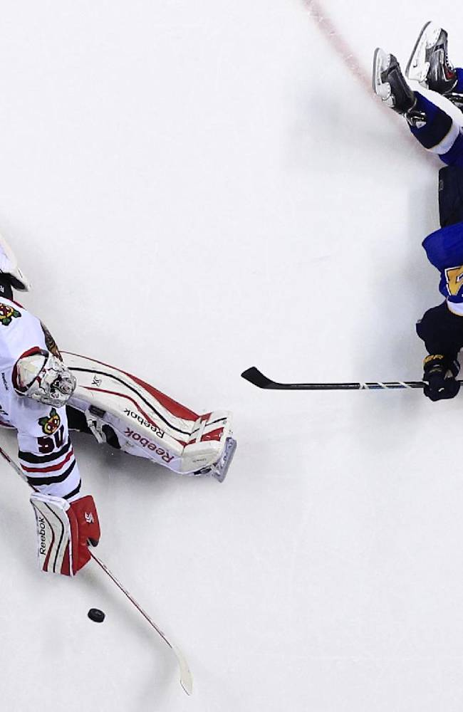 St. Louis Blues' T.J. Oshie, right, scores past Chicago Blackhawks goalie Corey Crawford during the second period in Game 5 of a first-round NHL hockey playoff series Friday, April 25, 2014, in St. Louis