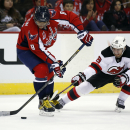 Washington Capitals left wing Alex Ovechkin (8), from Russia, controls the puck as New Jersey Devils center Jacob Josefson (16), from Sweden, reaches in the third period of an NHL hockey game, Friday, Nov. 14, 2014, in Washington. The Devils won 1-0 The A