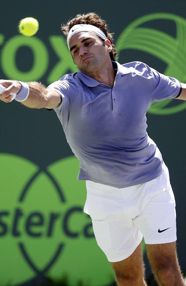 Roger Federer, of Switzerland, reaches for a return against Ivo Karlovic, of Croatia, during a match at the Sony Open tennis tournament, Friday, March 21, 2014, in Key Biscayne, Fla
