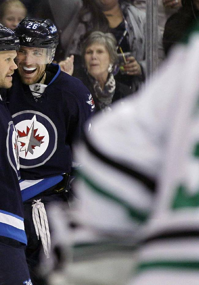 Winnipeg Jets' Olli Jokinen (12) and Blake Wheeler (26) celebrate Wheeler's goal against Dallas Stars' goaltender Kari Lehtonen (32) during second period of an NHL hockey game in Winnipeg, Manitoba, on Saturday, Dec. 14, 2013