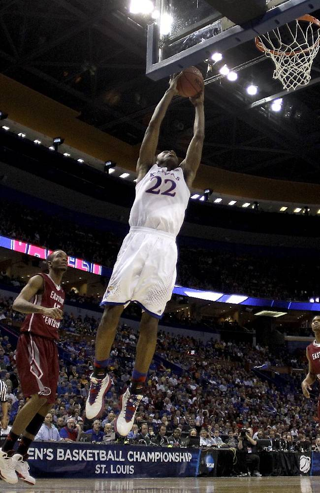 Kansas' Andrew Wiggins (22) gets past Eastern Kentucky's Orlando Williams, left, and Corey Walden (2) to dunk the ball during the first half of a second-round game in the NCAA college basketball tournament, Friday, March 21, 2014, in St. Louis