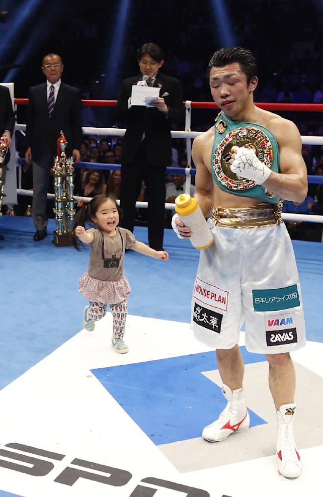 Akira Yaegashi of Japan poses for photographers as his daughter Shinobu runs up to him after winning the WBC flyweight title bout against Odilon Zaleta of Mexico in Tokyo, Sunday, April 6, 2014