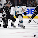 Los Angeles Kings defenseman Brayden McNabb, left, and San Jose Sharks center Tommy Wingels battle for the puck during the third period of an NHL hockey game, Wednesday, Oct. 8, 2014, in Los Angeles. The Sharks won 4-0 The Associated Press