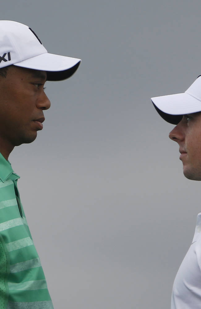 Tiger Woods, left, of the United States and Rory Mcllory of Northern Ireland pose before an exhibition golf match in Haikou, in southern China's island province Hainan, Monday, Oct. 28, 2013