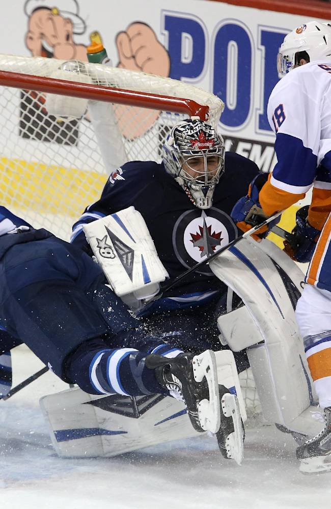 Winnipeg Jets' Mark Scheifele (55) is shoved into goaltender Ondrej Pavelec by New York Islanders' Ryan Strome (18) during the first period of an NHL hockey game in Winnipeg, Manitoba, Tuesday, March 4, 2014