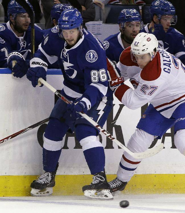 Tampa Bay Lightning right wing Nikita Kucherov, of Russia, flips the puck away from Montreal Canadiens center Alex Galchenyuk (27) during the first period of an NHL hockey game Tuesday, April 1, 2014, in Tampa, Fla
