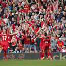 Liverpool's Jordan Henderson, right, celebrates with teammates after forcing an own goal by Tottenham's Younes Kaboul during their English Premier League soccer match at Anfield Stadium, Liverpool, England, Sunday March 30, 2014