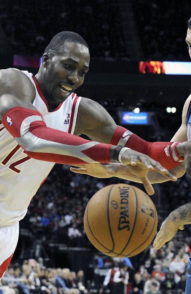 Houston Rockets' Dwight Howard (12) tries to maintain control of the ball under pressure from Minnesota Timberwolves' Nikola Pekovic in the second half of an NBA basketball game Saturday, Nov. 23, 2013, in Houston. The Rockets won 112-101