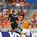 Houston Dynamo midfielder Brad Davis (11) goes up for a header against D.C. United midfielder/defender Perry Kitchen (23) during the first half of an MLS soccer match at BBVA Compass Stadium, Sunday, Oct. 12, 2014, in Houston The Associated Press
