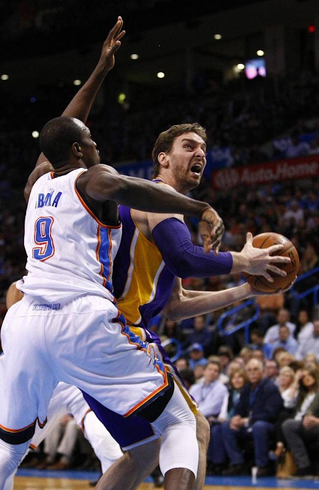 Oklahoma City Thunder forward Serge Ibaka (9) defends as Los Angeles Lakers center Pau Gasol (16) goes to the basket during the first quarter of an NBA basketball game in Oklahoma City, Thursday, March 13, 2014