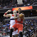 Chicago Bulls guard Jimmy Butler (21) goes to the basket against Washington Wizards center Marcin Gortat, back, of Poland, during the first half of an NBA basketball game, Saturday, April 5, 2014, in Washington The Associated Press