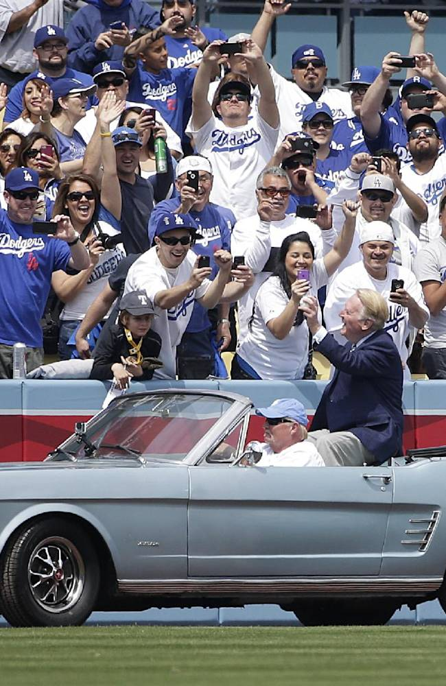 Los Angeles Dodgers broadcaster Vin Scully acknowledges fans as he arrives to throw the ceremonial first pitch for a baseball game between the Los Angeles Dodgers and the San Francisco Giants on Friday, April 4, 2014, in Los Angeles