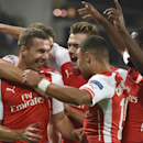 Teammates hug Arsenal's Lukas Podolski, left, after he scored the decisive goal setting the score at 2-1 during the Group D Champions League match between Anderlecht and Arsenal at Constant Vanden Stock Stadium in Brussels, Belgium, Wednesday Oct. 22, 201