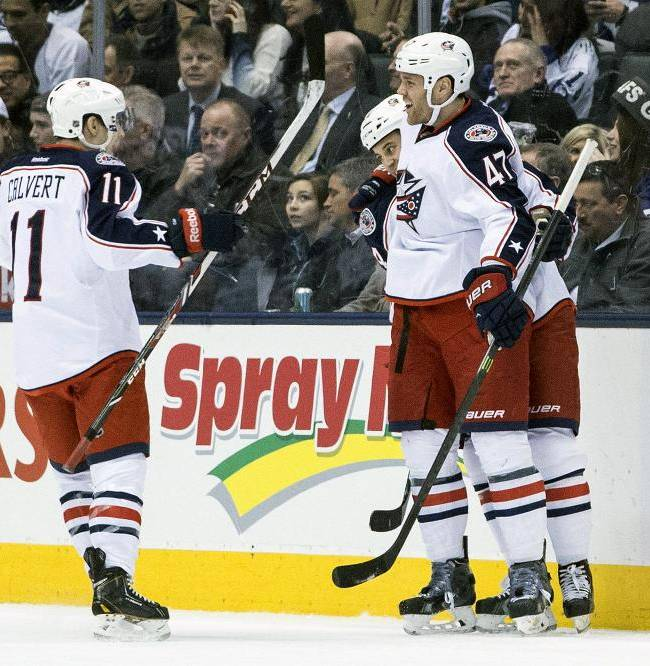 Columbus Blue Jackets Dalton Prout, right, celebrates with Derek MacKenzie, center, and Matt Calvert after Prout scored a goal against the Toronto Maple Leafs during the second period of an NHL hockey game in Toronto on Monday, March 3, 2014