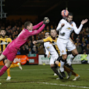 Cambridge United's goalkeeper Chris Dunn goes to punch the ball clear as Manchester United's Robin Van Persie heads for goal during their English FA Cup fourth round soccer match between Cambridge United and Manchester United, in Cambridge, England, Frida