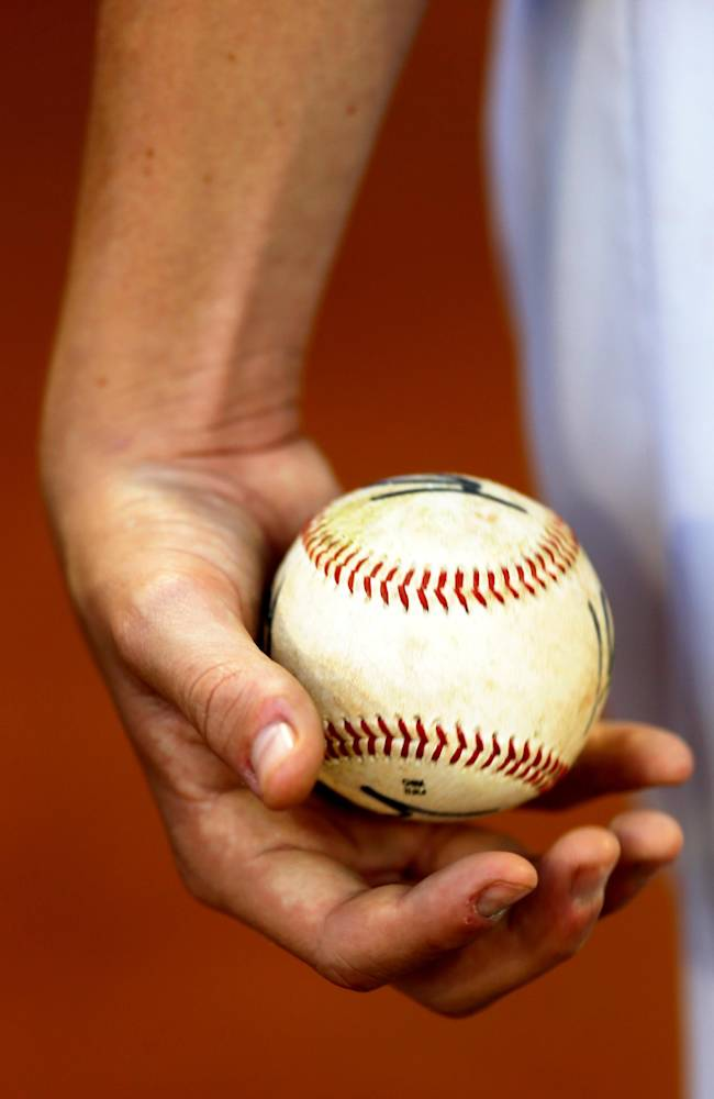 In this Nov. 27, 2013 photo, Tiburones of La Guaira's Anthony DeFrancesco of the U.S., tosses a baseball in his hand prior to a baseball game against rival Leones at Estadio Universitario in Caracas, Venezuela. It's about two months before pitchers and catchers report to spring training in the U.S., but in Venezuela the nation's fiercely competitive professional league is in full swing, and it's drawn the biggest contingent of American players in decades