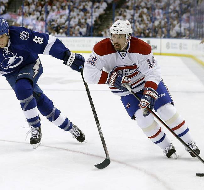 Montreal Canadiens center Tomas Plekanec (14), of the Czech Republic, gets ahead of Tampa Bay Lightning defenseman Sami Salo (6), of Finland, as he goes to the net during the first period of Game 2 of a first-round NHL hockey playoff series on Friday, April 18, 2014, in Tampa, Fla