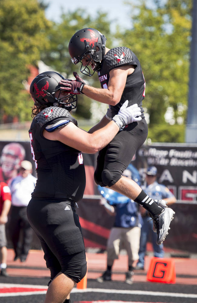 Eastern Washington's Jake Rodgers lifts wide receiver Blair Bomber after Bomber scored their first touchdown against Sam Houston State in the first half of an NCAA college football game in Cheney, Wash., Saturday, Aug. 23, 2014