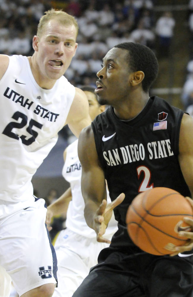 San Diego State guard Xavier Thames (2) drives to the basket as Utah State center Jordan Stone (25) defends in overtime of an NCAA college basketball game Saturday, Jan. 25, 2014, in Logan, Utah
