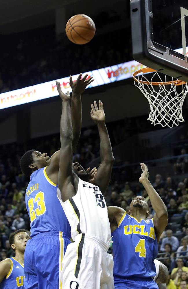 UCLA's Tony Parker, left, and Norman Powell, right, battle for a rebound with Oregon forward Richard Amardi during the first half of an NCAA college basketball game in Eugene, Ore., Thursday, Jan. 30, 2014. (AP Photo)