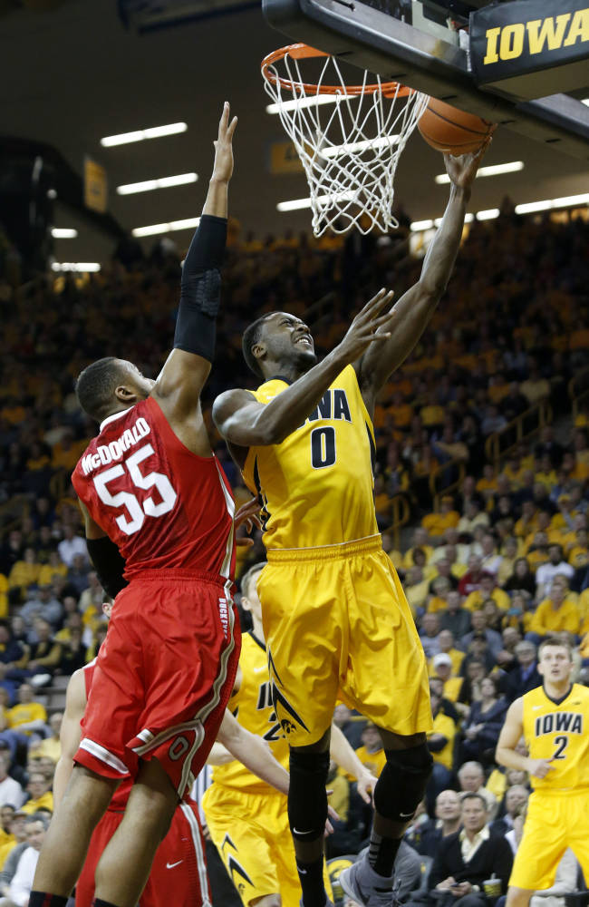 Ohio State center Trey McDonald (55) tries to stop a lay-up by Iowa's Gabriel Olaseni during the first half of an NCAA college basketball game Tuesday, Feb. 4, 2014, in Iowa City, Iowa