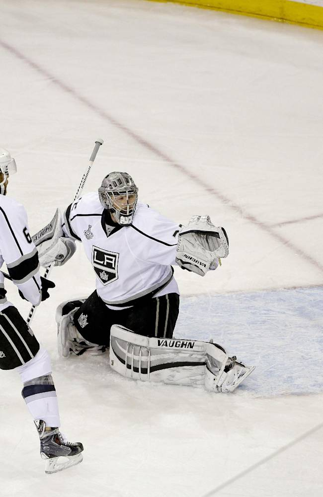 New York Rangers left wing Benoit Pouliot (67) redirects the puck past Los Angeles Kings goalie Jonathan Quick (32) for a goal as Los Angeles Kings defenseman Jake Muzzin (6) looks on in the first period during Game 4 of the NHL hockey Stanley Cup Final, Wednesday, June 11, 2014, in New York