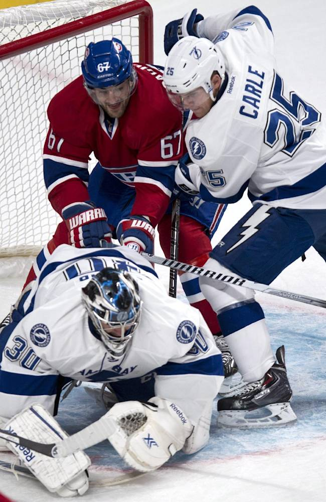 Tampa Bay Lightning defenseman Matt Carle tries to take out Montreal Canadiens' Max Pacioretty from behind goaltender Ben Bishop during the first period of an NHL hockey game Tuesday, Nov. 12, 2013, in Montreal