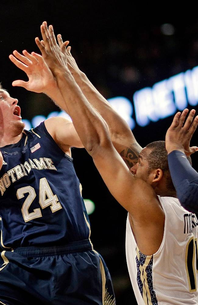 Notre Dame's Pat Connaughton, left, puts up a shot against Georgia Tech's Jason Morris, center, and Marcus Georges-Hunt, right, in the first half of an NCAA college basketball game, Saturday, Jan. 11, 2014, in Atlanta