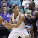 Utah Jazz's Enes Kanter, left, looks to pass as Charlotte Bobcats' Kemba Walker, rear, looks on as teammate Bismack Biyombo, right, defends, in the first quarter during an NBA basketball game, Friday, March 1, 2013, in Salt Lake City. (AP Photo/Rick Bowmer)