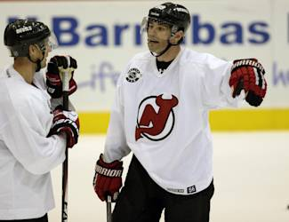 New Jersey Devils right wing Jaromir Jagr, right, of the Czech Republic, talks to Travis Zajac during NHL hockey training camp, Friday, Sept. 19, 2014, in Newark, N.J. (AP Photo/Julio Cortez)