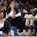 U.S. guard Derrick Rose, left, sits on the floor, next to forward Mason Plumlee and other teammates sitting on the bench during the second half of an exhibition basketball game at Madison Square Garden in New York, Wednesday, Aug. 20, 2014. Rose didn't play as the United States defeated the Dominican Republic 105-62. (AP Photo/Kathy Willens)