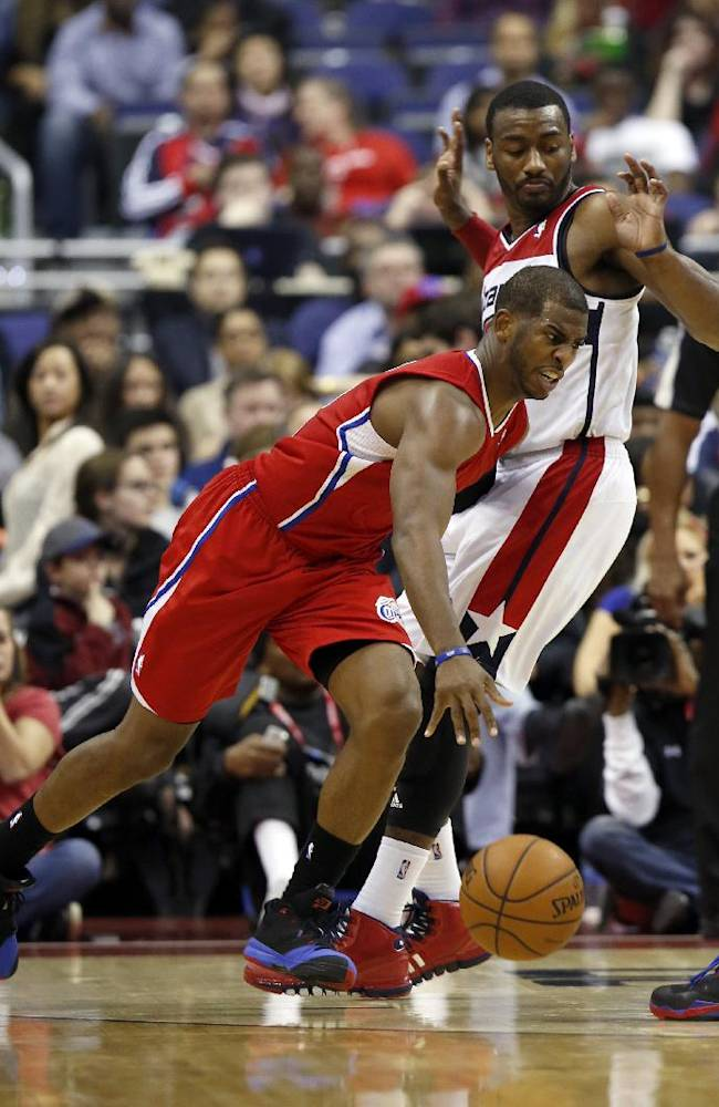 Los Angeles Clippers guard Chris Paul (3) drives past Washington Wizards guard John Wall (2) in the second half of an NBA basketball game, Saturday, Dec. 14, 2013, in Washington. The Clippers won 113-97
