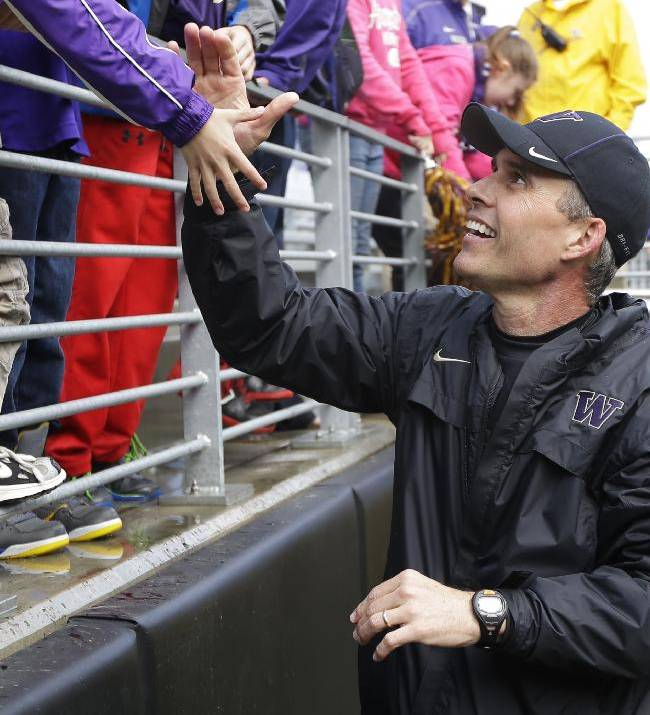 Washington coach Chris Petersen greets fans, Saturday, April 19, 2014, following Washington's spring NCAA college football preview in Seattle. The team held an open practice and limited scrimmage