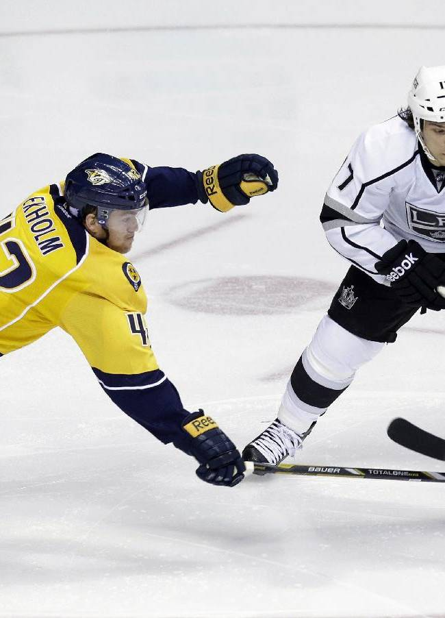 Nashville Predators defenseman Mattias Ekholm (42), of Sweden, knocks the puck away from Los Angeles Kings left wing Daniel Carcillo (17) during the third period of an NHL hockey game Thursday, Oct. 17, 2013, in Nashville, Tenn. The Kings won 2-1 in a shootout