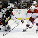 Washington Capitals' Marcus Johansson (90), of Sweden, clears the puck away from Pittsburgh Penguins' Lee Stempniak (22) during the second period of an NHL hockey game, Tuesday, March 11, 2014, in Pittsburgh. (AP Photo/Keith Srakocic)