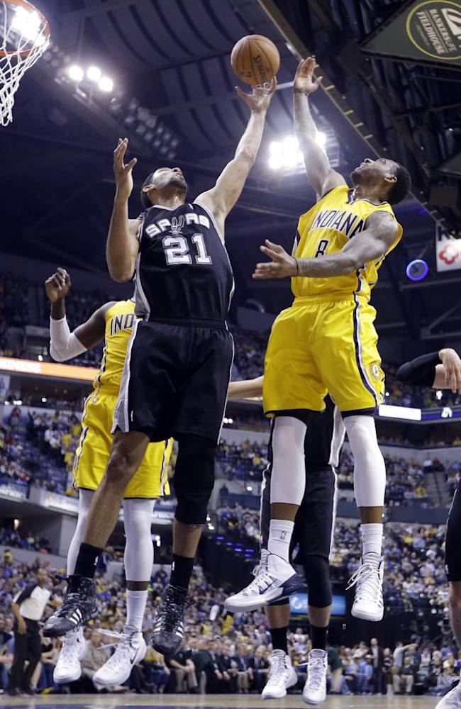 San Antonio Spurs forward Tim Duncan (21) grabs a rebound in front of Indiana Pacers guard Rasual Butler in the first half of an NBA basketball game in Indianapolis, Monday, March 31, 2014