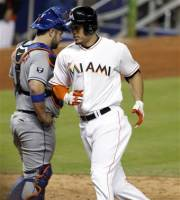 Miami Marlins' Giancarlo Stanton, right, crosses home after hitting a home run as New York Mets catcher Kelly Shoppach (6) looks past in the sixth inning of a baseball game in Miami, Monday, Oct. 1, 2012. The Marlins won 3-2. (AP Photo/Alan Diaz)