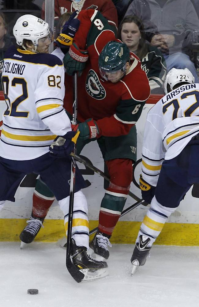 Minnesota Wild defenseman Marco Scandella, center, is held away from the puck by Buffalo Sabres' Marcus Foligno, left, and Johan Larsson (22), of Sweden, during the third period of an NHL hockey game in St. Paul, Minn., Thursday, Jan. 2, 2014. The Wild won 4-1