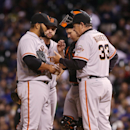 San Francisco Giants pitching coach Dave Righetti, front right, confers with relief pitcher Yusmeiro Petit, front left, as second baseman Brandon Hicks, back left, and catcher Buster Posey look on after Petit gave up a double to Colorado Rockies' DJ LeMah