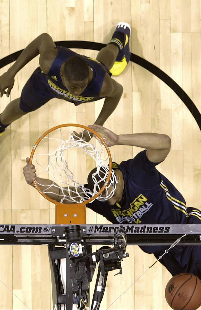 Michigan's Jordan Morgan dunks as Caris LeVert watches during practice for their NCAA Midwest Regional semifinal college basketball tournament game Thursday, March 27, 2014, in Indianapolis. Michigan plays Tennessee on Friday, March 28, 2013. (AP Photo/David J. Phillip)