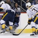 Winnipeg Jets' TJ Galiardi, center, and Nashville Predators' Shea Weber, left, fight for the puck during the second period of an NHL hockey game Tuesday, Nov. 4, 2014, in Winnipeg, Manitoba The Associated Press