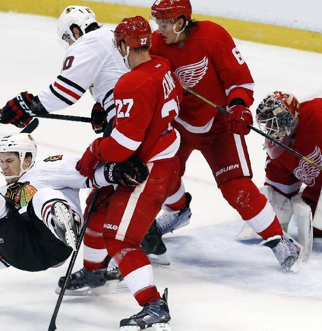 Chicago Blackhawks center Andrew Shaw, left, is taken down by Detroit Red Wings defenseman Kyle Quincey (27) in front of the net in overtime during an NHL hockey game Wednesday, Jan. 22, 2014, in Detroit. Detroit won 5-4 in a shootout