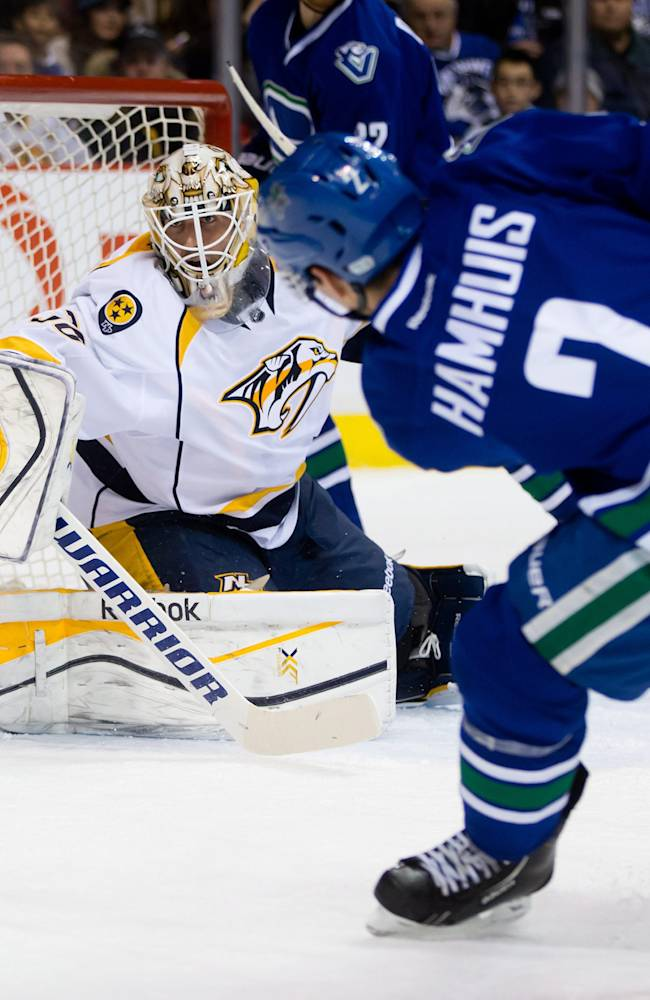 Nashville Predators goalie Carter Hutton, left, stops a shot by Vancouver Canucks' Dan Hamhuis during first period NHL hockey action in Vancouver, British Columbia on Thursday Jan, 23, 2014