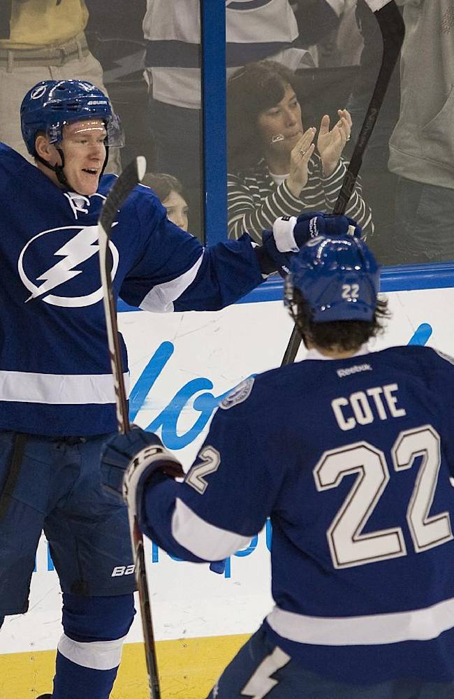 Tampa Bay Lightning's Radko Gudas (7), Jean-Philippe Cote (22) and Martin St. Louis (26) celebrate with Ondrej Palat after his goal against the New York Rangers during the first period of an NHL hockey game, Sunday, Dec. 29, 2013, in Tampa, Fla