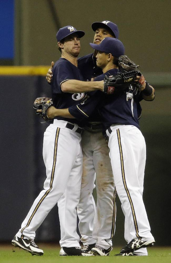 Milwaukee Brewers' Logan Schafer, left, Carlos Gomez and Norichika Aoki (7) celebrate after the ninth inning of a baseball game against the St. Louis Cardinals, Sunday, Sept. 22, 2013, in Milwaukee. The Brewers won 6-4
