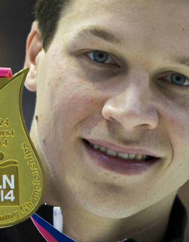 Gold medal winner ,Germany's Patrick Hausding, shows his medal after the men's 3m springboard diving final at the LEN Swimming European Championships in Berlin, Germany, Thursday, Aug. 21, 2014