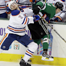 Edmonton Oilers defenseman Jeff Petry (2) and Dallas Stars left wing Jamie Benn crash into the boards during the second period of an NHL hockey game Sunday, Dec. 1, 2013, in Dallas The Associated Press